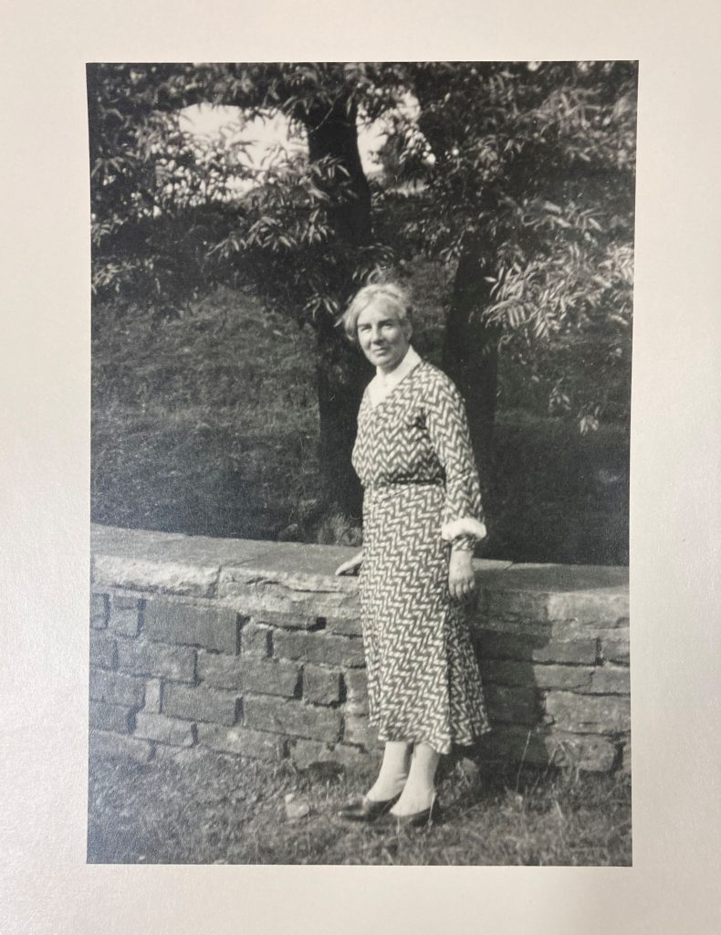 View of Dora Yates standing near a wall.